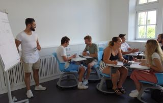 Ein Student präsentiert einer Gruppe von Studierenden etwas auf einem Flipchart.