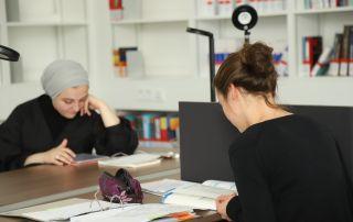 Zwei Studentinnen sitzen in der Bibliothek des Campus Rothenburg und lernen.