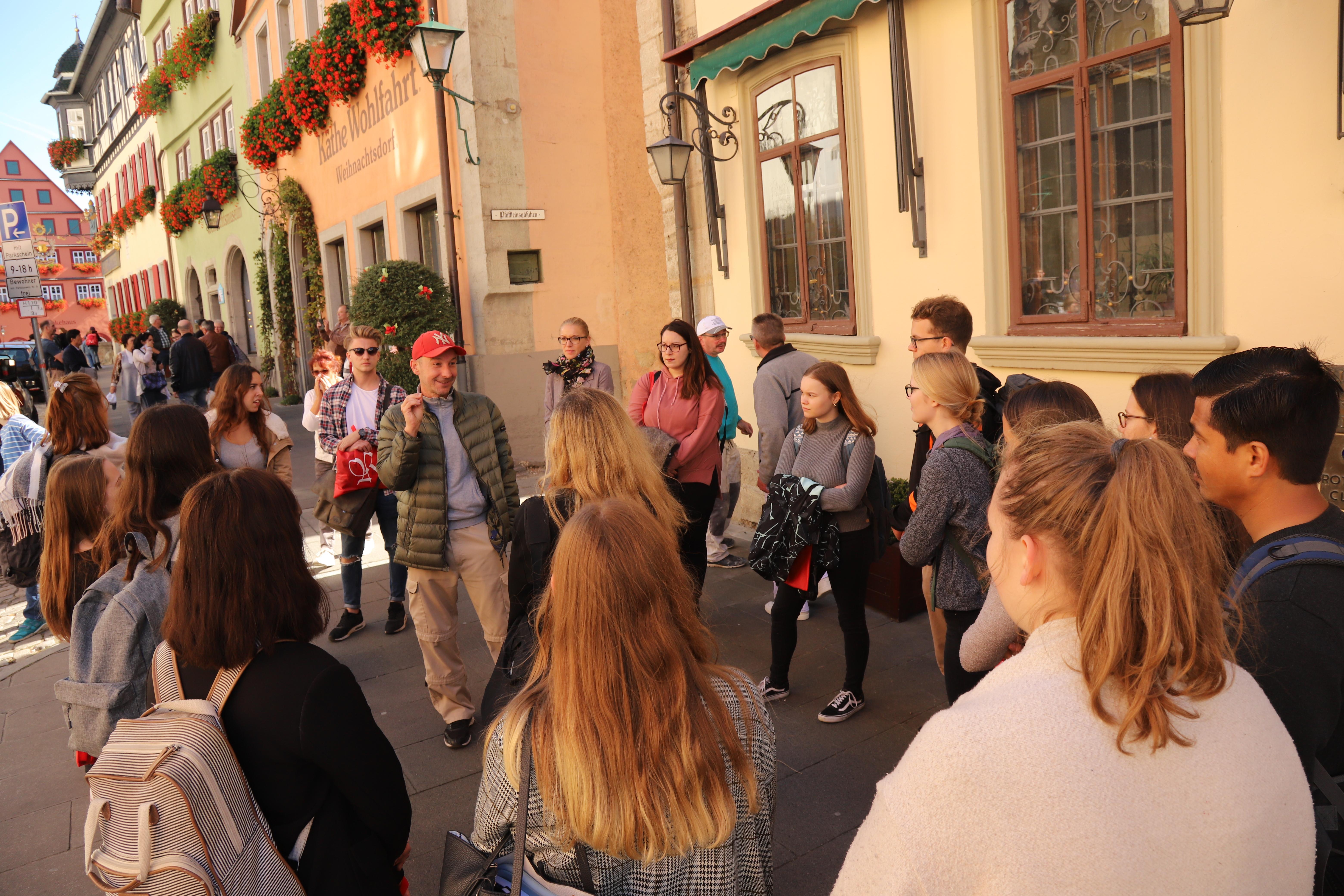Studierende lauschen bei einer Stadtführung durch Rothenburg den Worten des Gästeführers.