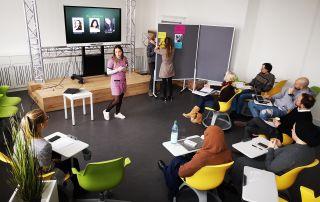 Zwei Studentinnen präsentieren vor einem gemischten Plenum ein Referat mit Hilfe von Smartboard und Pinnwand.