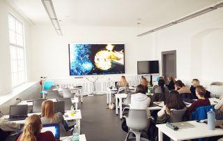 Blick von hinten auf Studierende, die in einem der Mediaräume des Campus Rothenburg vor einem sehr großen Bildschirm sitzen.