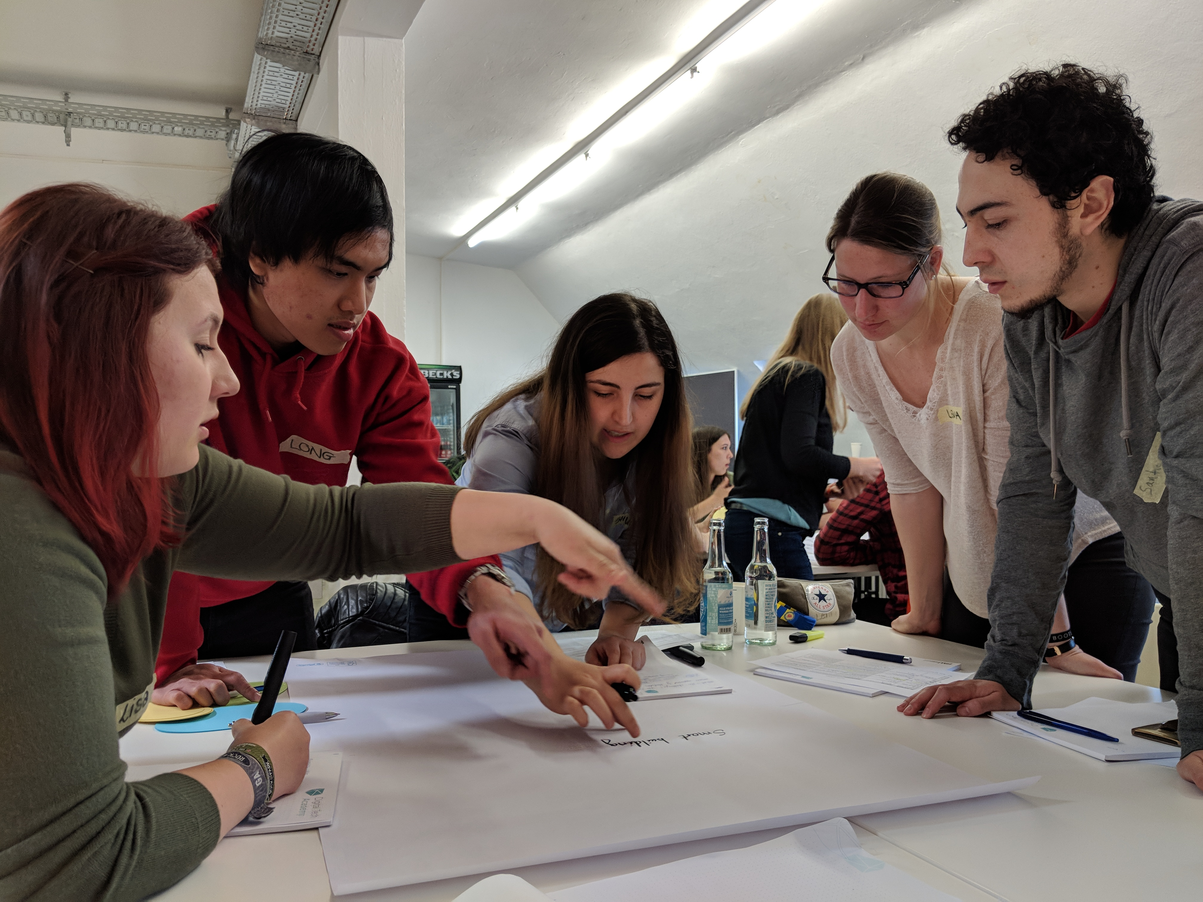 Eine Gruppe Studierender arbeitet gemeinsam an einem auf einem Tisch liegenden Chart.