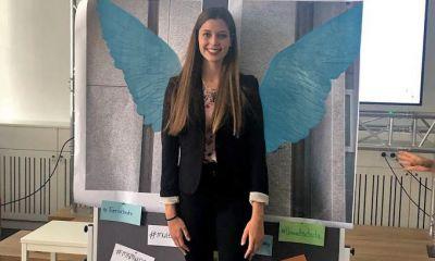 Eine Studierende posiert vor einer Leinwand mit Collette Miller-Flügeln